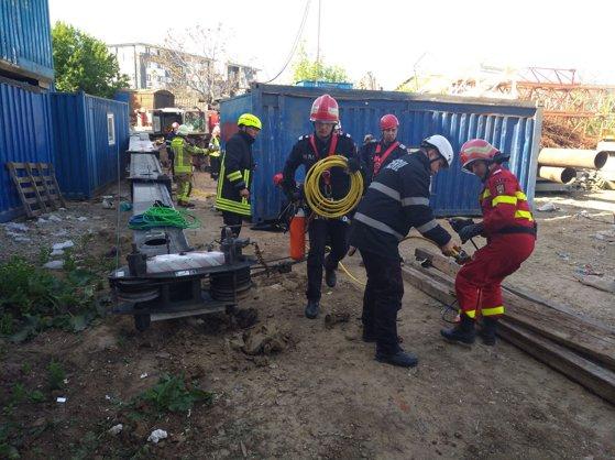 Imaginea articolului FOTO Operaţiunea de salvare contra cronometru a eşuat. Bărbatul prins sub un container pe un şantier din Bucureşti a fost scos decedat