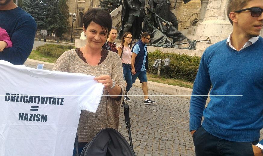 Protest faţă de vaccinarea obligatorie, la Cluj-Napoca. O tânără a afişat mesajul `Obligativitate = nazism`  | GALERIE FOTO
