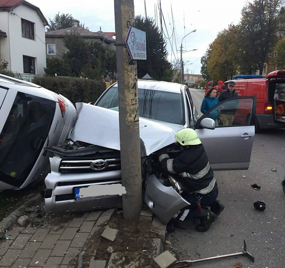 Accident desprins parcă dintr-o cascadorie: Doi stâlpi puşi la pământ şi o maşină răsturnată, după ce un autoturim a părăsit şoseaua - GALERIE FOTO