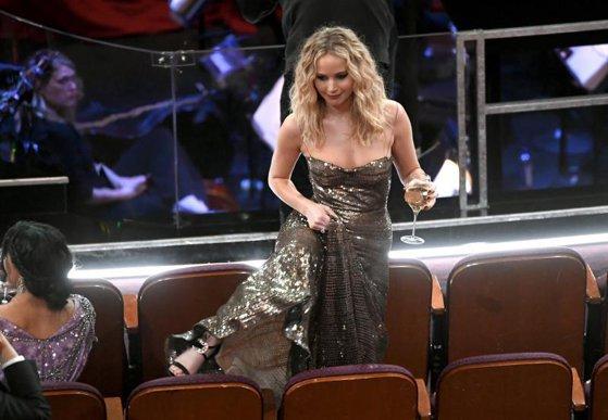Imaginea articolului Momente la Oscar 2018: Escalada lui Jennifer Lawrence în căutarea locului său. Actriţa, îmbrăcată într-o rochie lungă, purta tocuri înalte şi avea un pahar de vin în mână