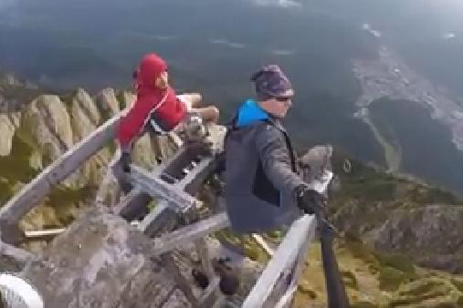 Echilibristică pe vârful Crucii Caraiman. Gestul extrem la care au recurs doi tineri, din dorinţa de a se filma pe monumentul înalt. VIDEO