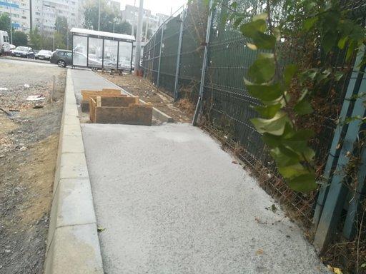 Trotuar construit în spatele unei staţii de autobuz până într-un gard