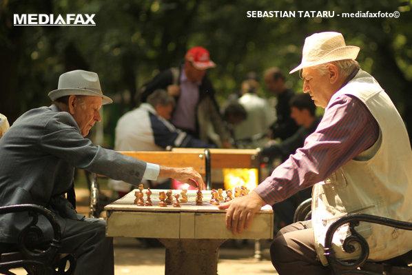 Pensionari joacă șah în parc