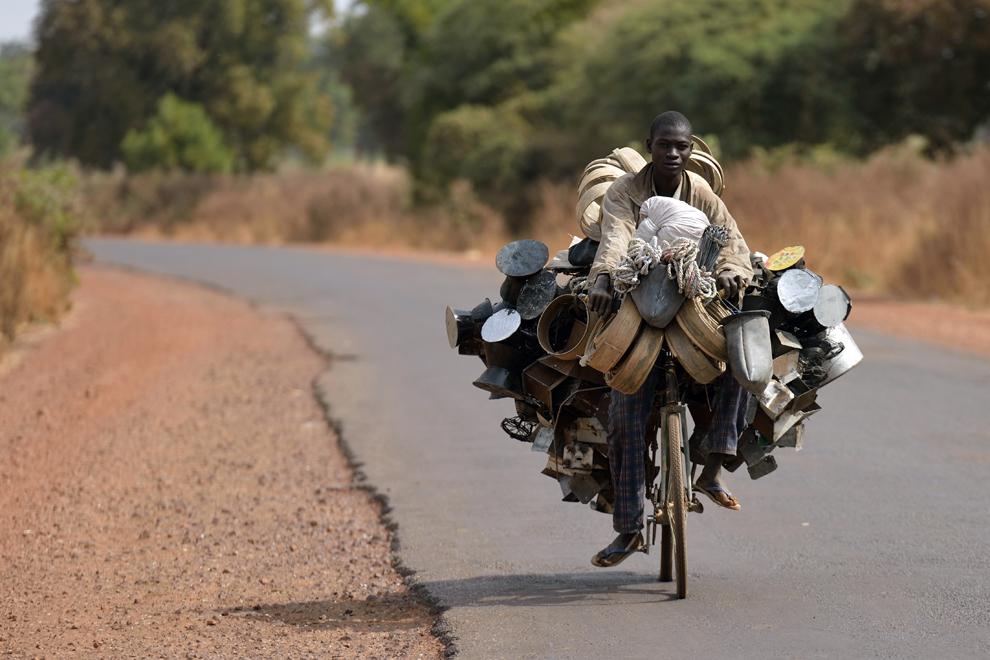 Un bărbat cară pe bicicletă diverse bunuri pe care doreşte să le vânda la piaţă, lânga oraşul Segou, la 240km nord de Bamako, în Mali, marţi 22 ianuarie 2013.