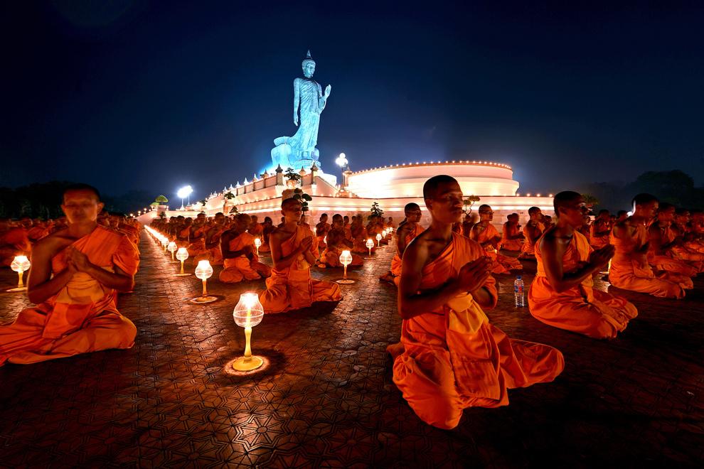 Călugări budişti tailandezi şi străini aprind lumânări si se roagă lângă statuia lui Budha, în provincia Nakorn Pathom, Thailanda, marţi, 22 ianuarie 2013.