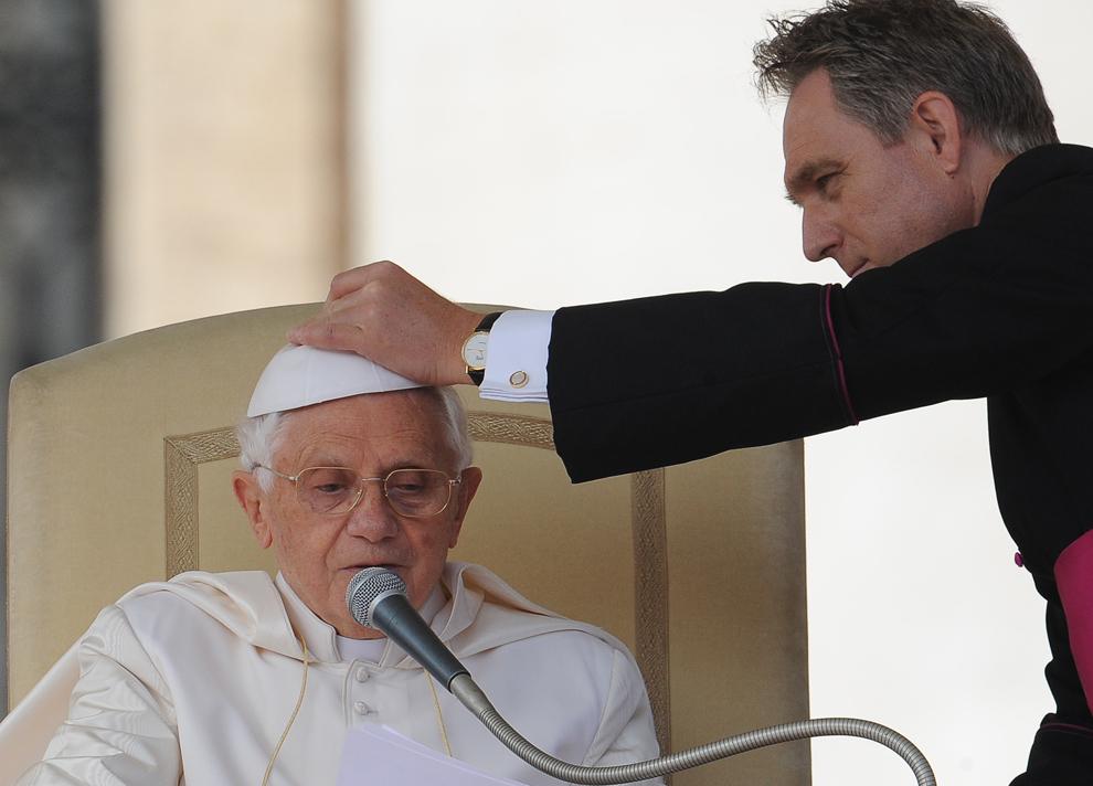 Secretarul personal al Papei Benedict al XVI-lea, Georg Gaenswein îi aşează tichia după ce aceasta a fost luată de vânt, în timpul audienţei generale săptămânale, în Vatican, miercuri, 20 octombrie 2012.