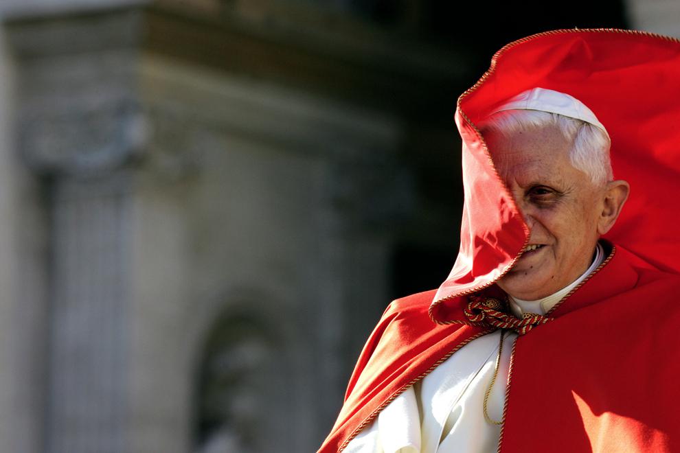 Papa Benedict al XVI-lea zâmbeşte în timp ce vântul îi zboară capa roşie, în timpul audienţei sale generale din piaţa Sfântul Petru, în Vatican, miercuri, 23 noiembrie 2005.