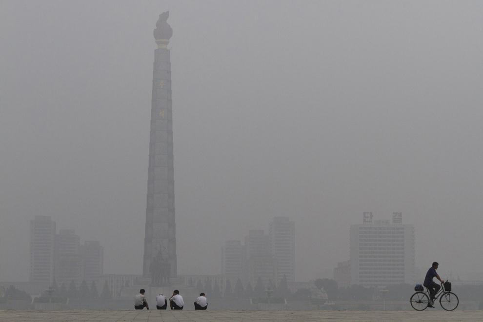 Locuitori ai Phenian-ului pot fi observaţi lângă râul Taedong, privind înspre turnul Juche, miercuri, 10 august 2011.