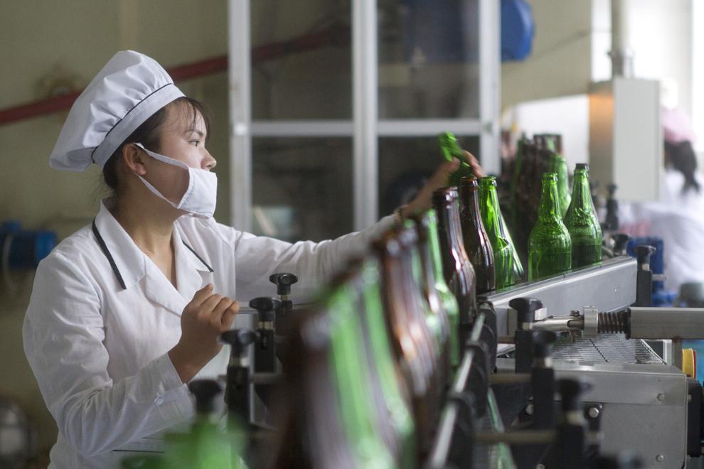 O muncitoare de la fabrica de îmbuteliere a apei minerale Kangso verifică linia de producţie, în Nampo, Coreea de Nord, marţi, 16 august 2011. Mica fabrică este prezentată vizitatorilor pentru a demonstra înaltul grad de tehnologizare al industriei nord coreene.