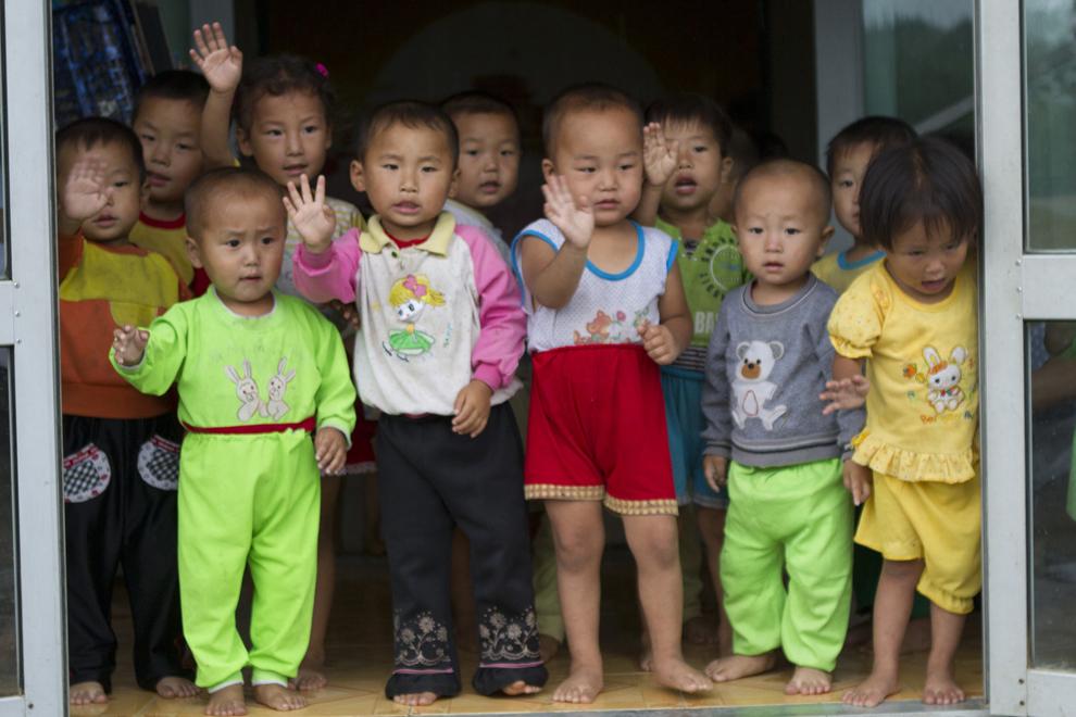 Un grup de copii de vârstă preşcolară nord-coreeni salută turiştii occidentali care vizitează ferma cooperatistă Chosan, lângă Wonsan, august 2011.