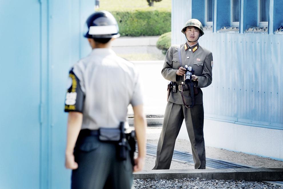 Un soldat nord-coreean având un aparat foto în mână, priveşte înspre un soldat sud-coreean, în zona demilitarizată ce separă cele doua Corei, în Panmunjom, vineri, 1 iunie 2012