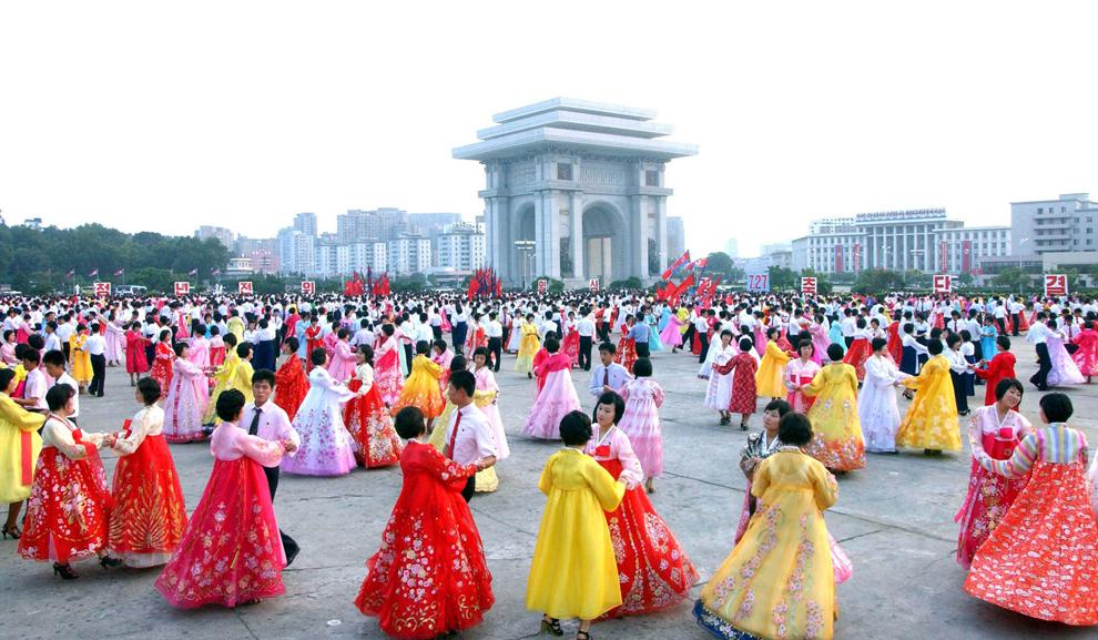 Studenţi şi tineri nord-coreeni dansează la o dată nespecificată, în faţa Teatrului Poporului din Phenian, pentru a sărbători a 59-a aniversare a 'victoriei' Coreei de Nord în războiul din Coreea.