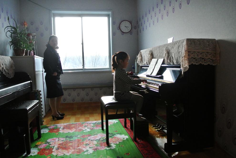 O fetiţă nord-coreeană cântă la pian în timpul unei ore de muzică, în timp ce este supravegheată de o profesoară, într-o grădiniţă din oraşul Siniuju, în apropierea graniţei cu China, sâmbătă, 15 decembrie 2012.