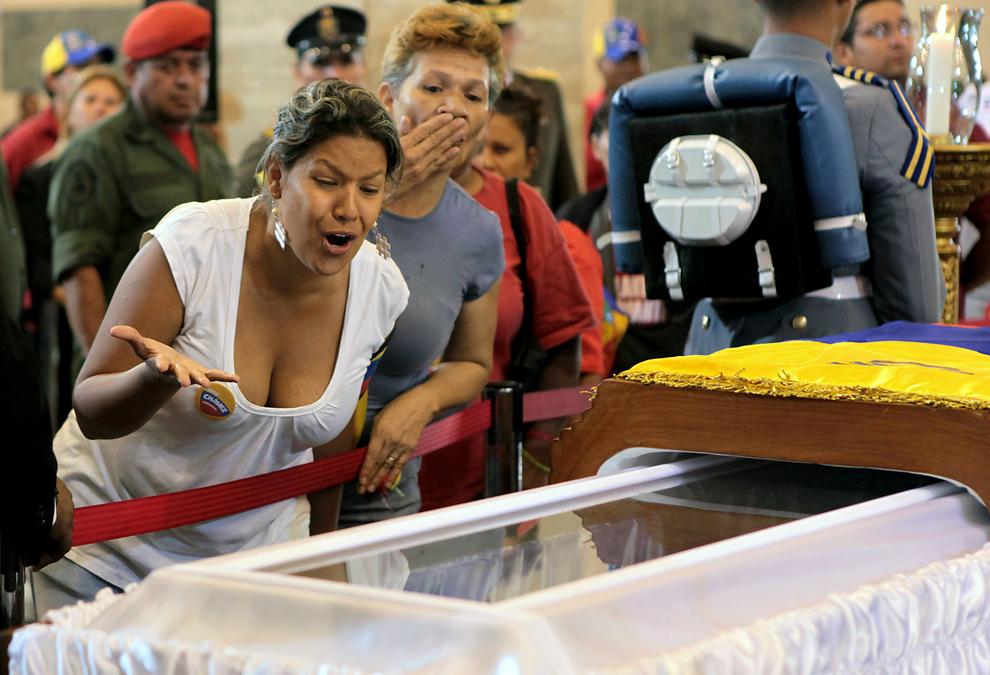 O femeie reacţionează în timp ce-şi aduce un ultim omagiu liderului venezuelean Hugo Chavez, la capela Academiei Militare din Caracas, Venezuela, joi, 7 martie 2013.