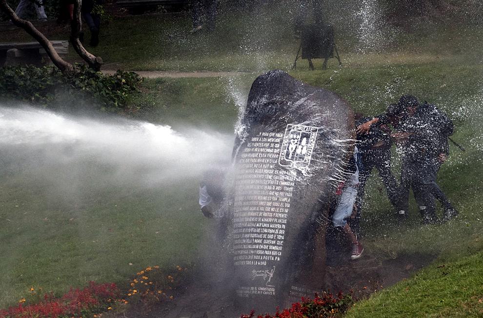 Mai mulţi studenţi se apără de un tun cu apă, în timpul confruntărilor cu forţele de ordine, în Santiago de Chile, Chile, joi, 7 martie 2013. Studenţii protestează pentru îmbunătăţirea sistemului public de educaţie.
