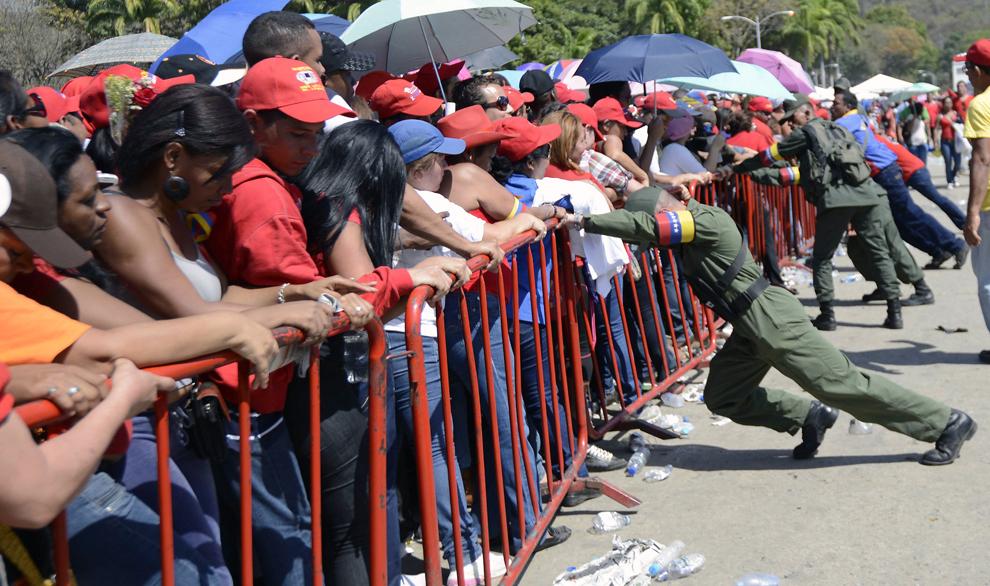 Soldaţi venezueleni sprijină gardul protector instalat în faţa Academiei Militare din Caracas, joi, 7 martie 2013. Mii de oameni au venit pentru a-i aduce un ultim omagiu fostului lider, Hugo Chavez.