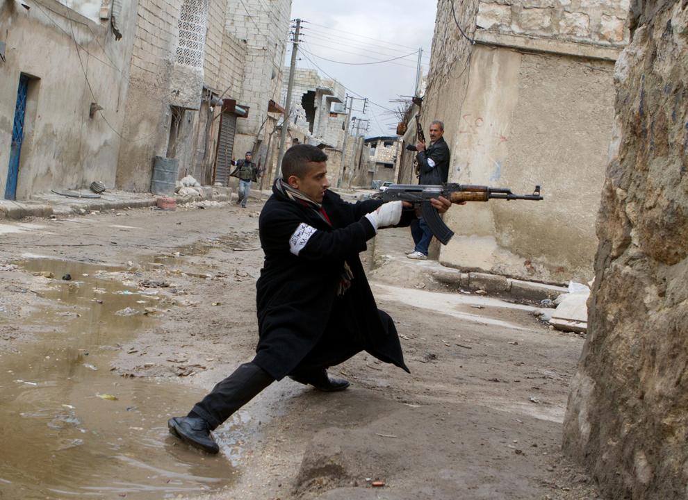 Un rebel sirian luptă împotriva forţelor guvernamentale pe o stradă de lângă aeroportul internaţional din Alep, luni, 4 martie 2013.