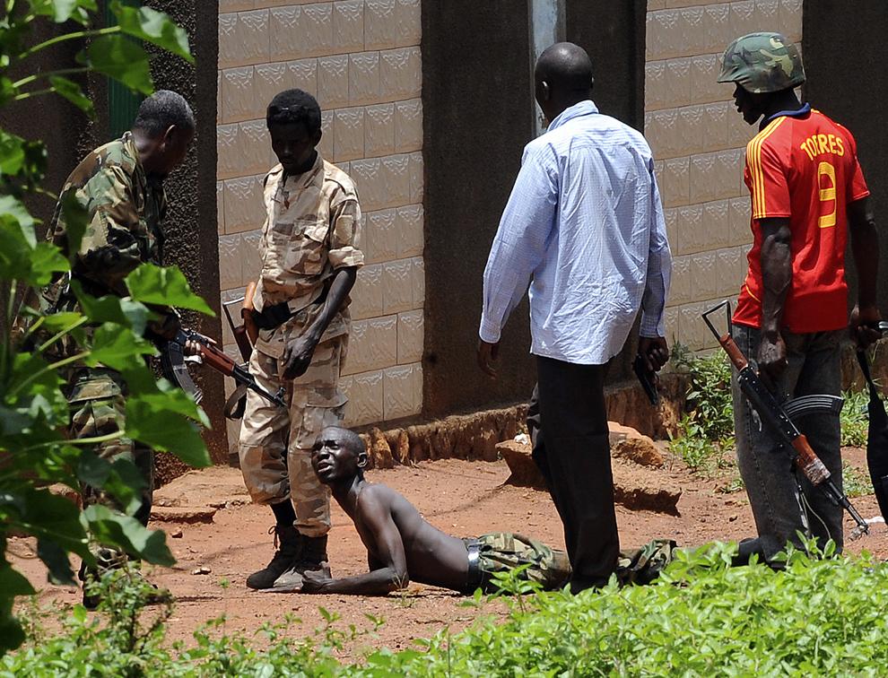 Rebelii din coaliţia Seleka arestează un bărbat ce poartă uniformă militară, suspectat de jefuirea unei case într-o zonă populară din Bangui, Republica Centrafricană, marţi, 26 martie 2013.