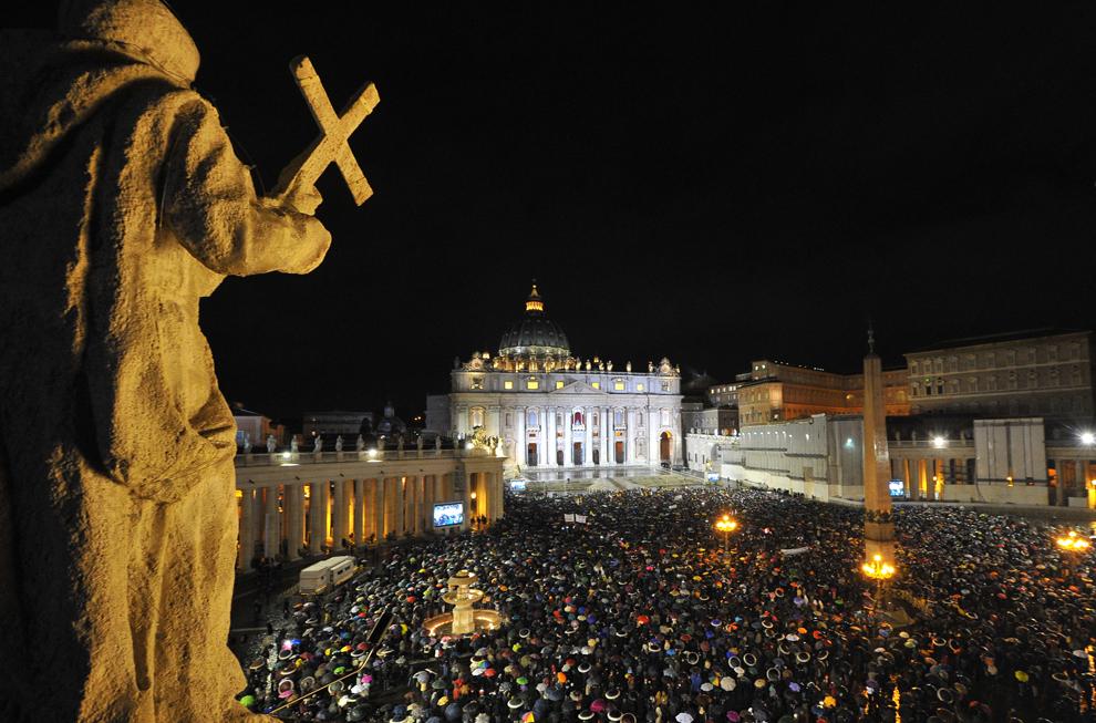 Mulţimea de credincioşi, care aşteaptă alegerea noului Papă, poate fi văzută în Piaţa Sfântul Petru din Roma, în timp ce pe coşul Capelei Sixtine iese fum alb, miercuri, 13 martie 2013.