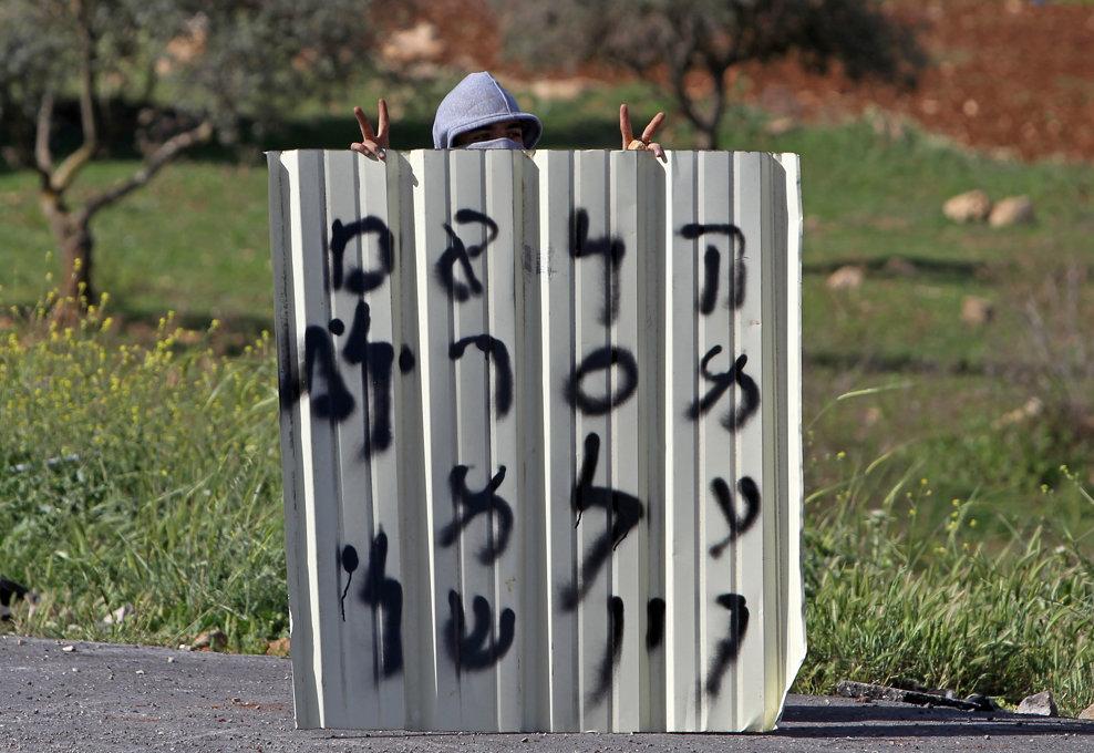 Un protestatar palestinian arată semnul victoriei din spatele unei baricade improvizate în timpul ciocnirilor cu forţele de securitate israeliene, în apropierea închisorii Ofer, aproape de Ramallah, după decesul unui deţinut paletinian, miercuri, 3 aprilie 2013.