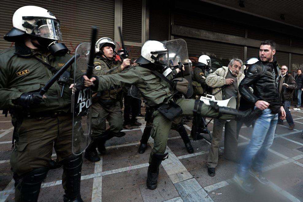 Poliţişti greci atacă un mic grup de sindicalişti comunişti care protestează în faţa ministerului Muncii împotriva noilor planuri de reducere a pensiilor, în Atena, miercuri, 30 ianuarie 2013.