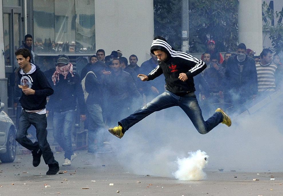 Un protestatar tunisian sare peste o petardă fumigenă trasă de poliţişti în timpul unui miting în faţa ministerului de Interne, după ce Chokri Belaid, lider al opoziţiei şi critic deschis al guvernului, a fost împuşcat mortal, miercuri, 6 februarie 2013.