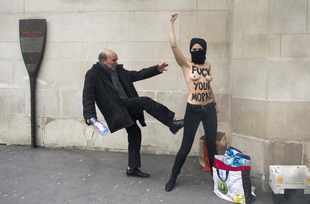 Un bărbat loveşte o activistă topless a mişcării feministe ucrainiene Femen în timp ce aceasta ridică pumnul pentru a protesta împotriva islamiştilor radicali, în faţa Marii Moschei a Parisului, în Paris, miercuri, 3 aprilie 2013.
