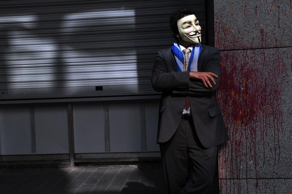 Un protestatar purtând o mască Guy Fawkes stă în apropierea ministerului Finanţelor din Atena, în timp ce membri şi suporteri ai partidului 'Grecii Independenţi' participă la un protest, în aşteptarea sosirii reprezentanţilor troicii UE-FMI-BCE, în Atena, joi, 4 aprilie 2013.