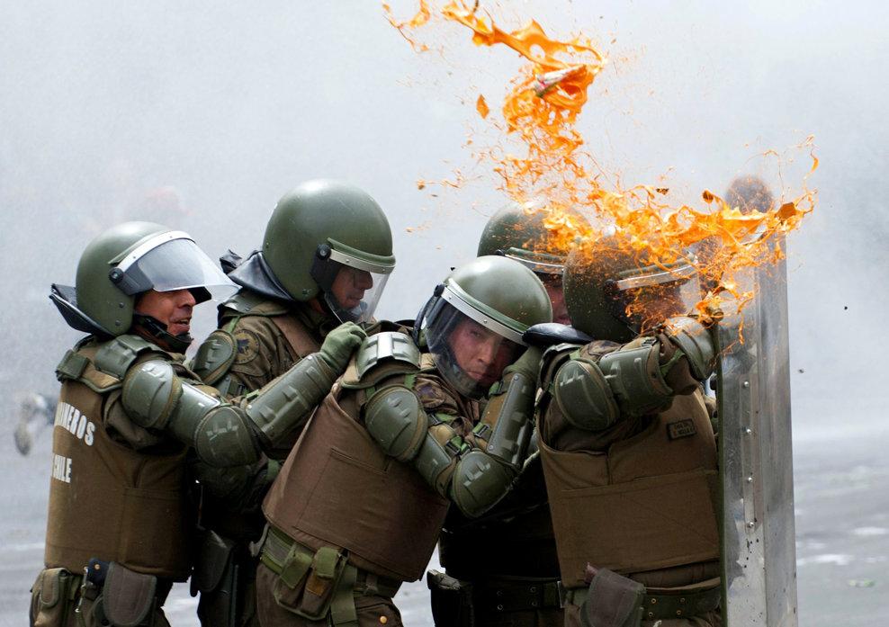 Poliţişti chilieni se adăpostesc în spatele scuturilor în timpul unor ciocniri cu studenţii care militează pentru îmbunătăţirea sistemului public de educaţie, în Santiago, joi, 7 martie 2013.