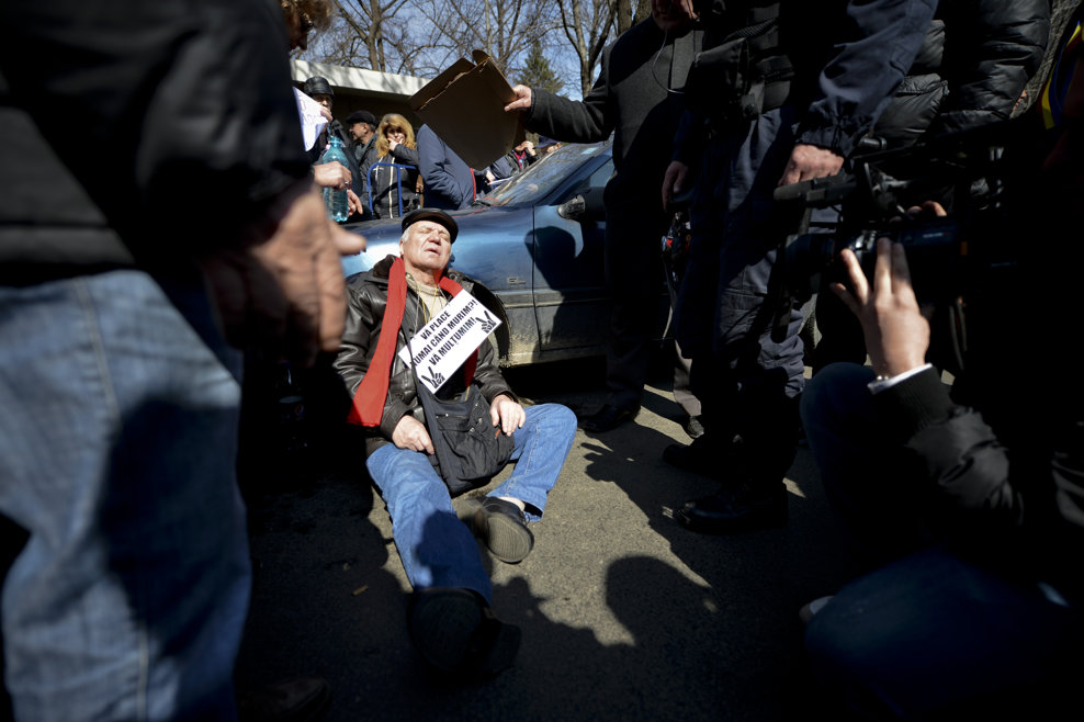 Un bărbat căruia i s-a facut rău este sprijinit de o maşină, în aşteptarea sosirii unei ambulanţe, în timpul protestului organizat de Sindicatul Revoluţionarilor din Decembrie 1989, în faţa Palatului Victoria din Bucureşti, luni, 18 martie 2013.