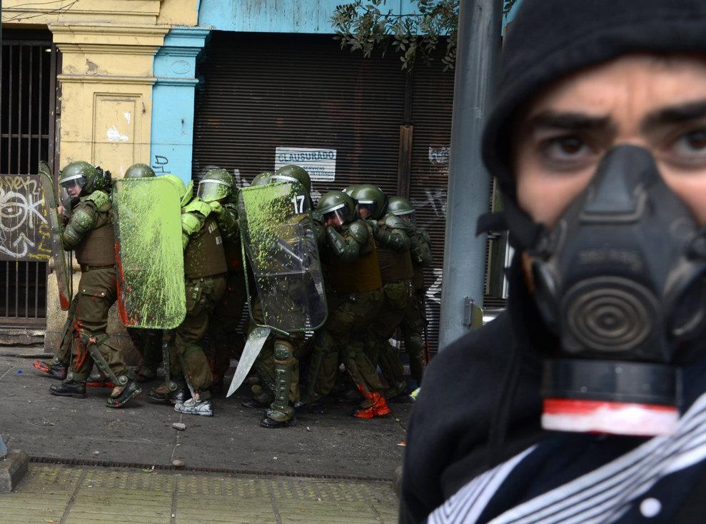 Mai mulţi poliţişti se apără cu scuturi în timpul unor ciocniri cu studenţii care cer guvernului preşedintelui Sebastian Pinera să îmbunătăţească calitatea sistemului de educaţie public, în Santiago, joi, 11 aprilie 2013.