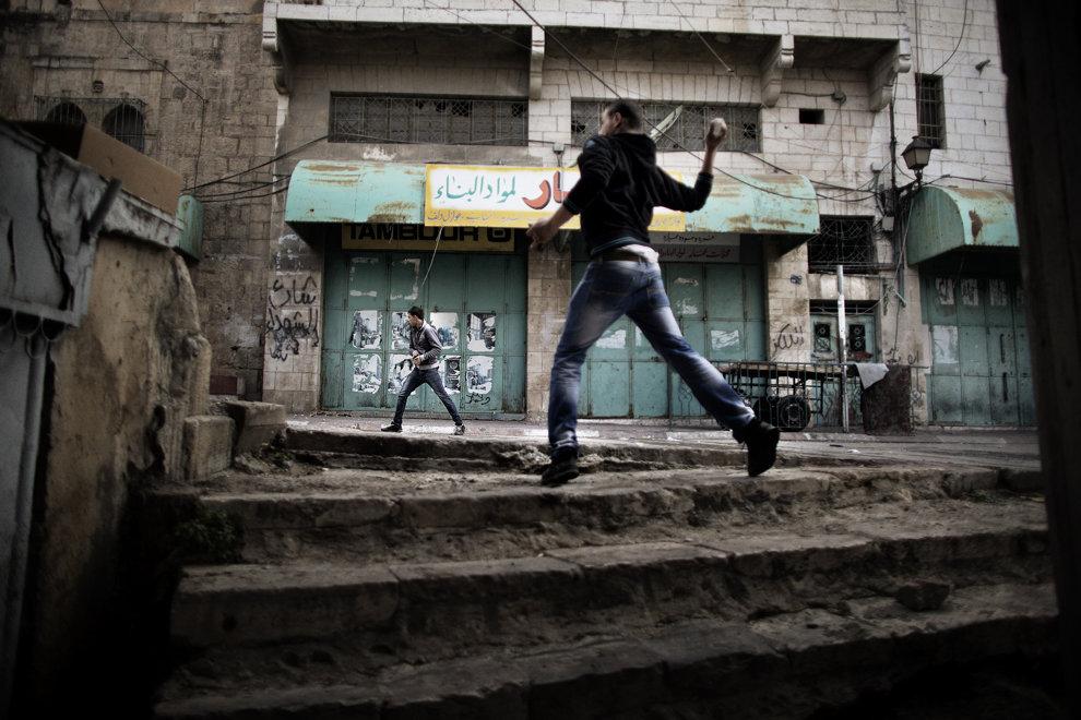 Doi protestatari palestinieni, care cer redeschiderea străzii Shuhada din oraşul vechi al Hebronului, închisă în 1994 şi considerată a fi inima oraşului, aruncă cu pietre în trupele israeliene în timpul unor ciocniri, vineri, 1 decembrie 2013.