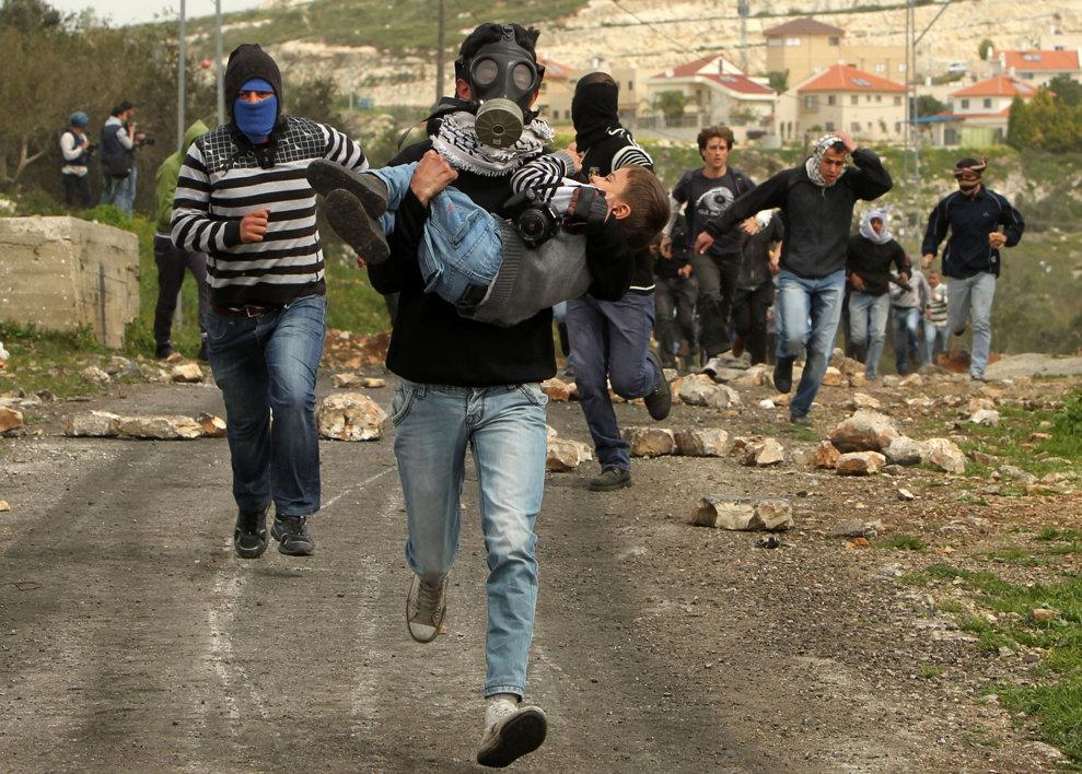 Un protestatar palestinian aleargă purtând în braţe un copil în timpul ciocnirilor cu forţele de securitatea israeliene ce au urmat unui protest împotriva exproprierii de către Israel a pământurilor aparţinînd palestinienilor, în satul Kafr Qaddum, lângă Nablus, vineri, 8 martie 2013.