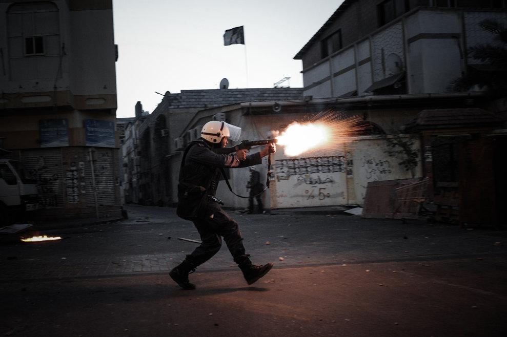 Un poliţist trage cu gaze lacrimogene spre protestatari antiguvernamentali în timpul unor ciocniri care au urmat unui protest provocat de uciderea lui Mahmud al-Jaziri de către forţele de ordine, în satul Daih, la vest de Manama, vineri, 8 martie 2013.