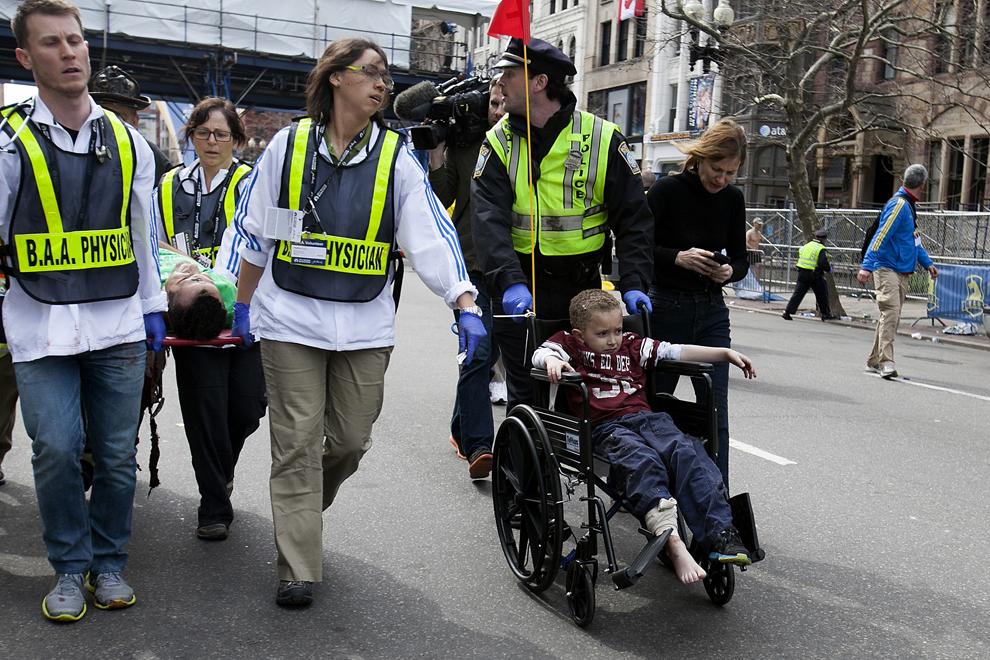 Echipaje de prim ajutor îngrijesc un copil într-un cărucior cu rotile, după ce două explozii au avut loc aproape de linia de sosire a celui de-al 117-lea Maraton Boston, luni, 15 aprilie 2013.