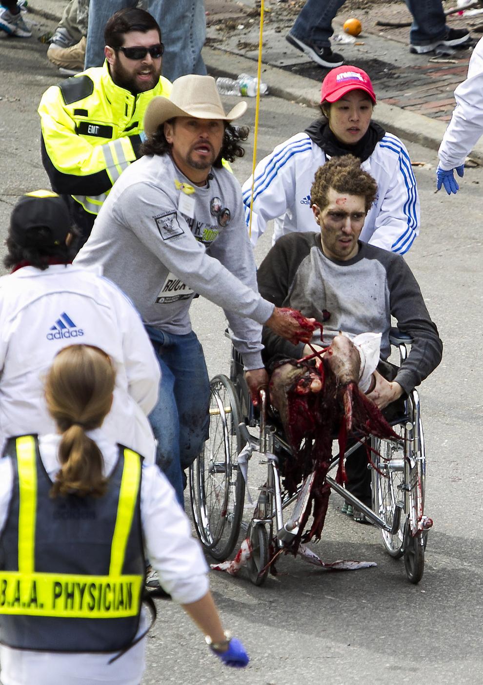 Echipaje de prim ajutor îngrijesc un bărbat rănit, după ce două explozii au avut loc aproape de linia de sosire a celui de-al 117-lea Maraton Boston, luni, 15 aprilie 2013.