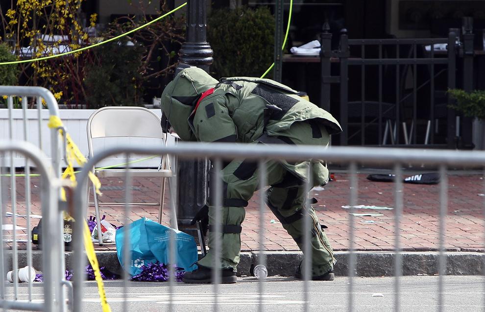 Un genist investighează un obiect suspect, aproape de locaţia celor două explozii, în Boston, luni, 15 aprilie 2013.