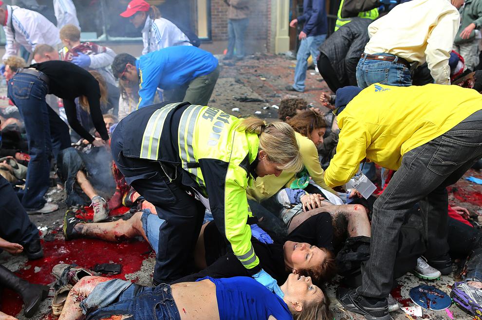 Persoane rănite în timpul primei explozii sunt aşezate pe trotuar, în timp ce medicii evaluează starea lor, aproape de linia de sosire a celui de-al 117-lea Maraton Boston, luni, 15 aprilie 2013.