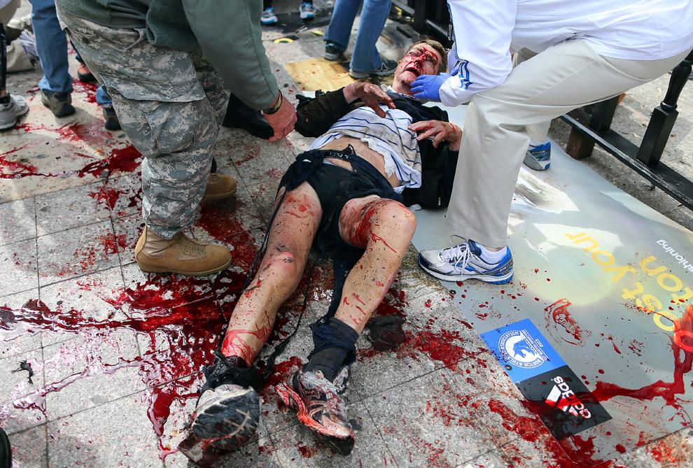 Un bărbat rănit în prima explozie este ajutat să se ridice de pe trotuar, după ce două explozii au avut loc aproape de linia de sosire a celui de-al 117-lea Maraton Boston, luni, 15 aprilie 2013.
