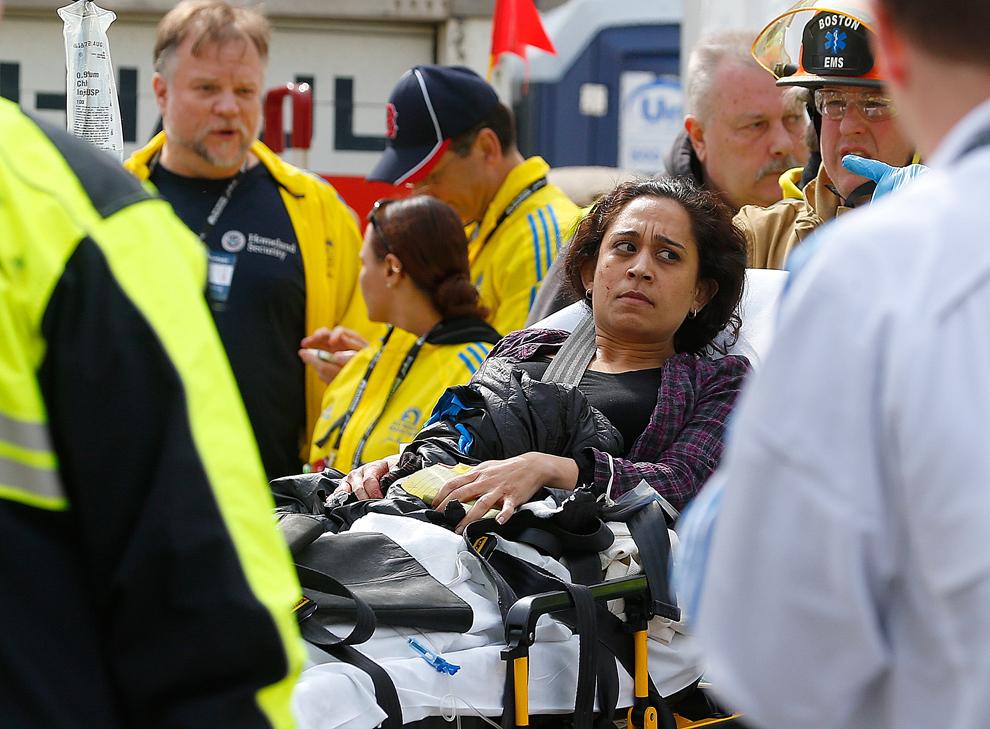 O femeie rănită este urcată într-o ambulanţă, după ce două explozii au avut loc aproape de linia de sosire a celui de-al 117-lea Maraton Boston, luni, 15 aprilie 2013.