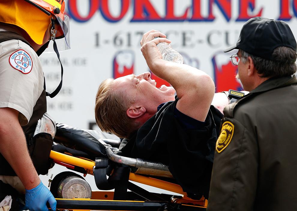Un bărbat este urcat într-o ambulanţă după ce a fost rănit de una dintre cele două bombe care au explodat în timpul celei de-a  117-a ediţii a Maratonului din Boston, lângă piaţa Copley, luni, 15 aprilie 2013, în Boston, Massachusetts.
