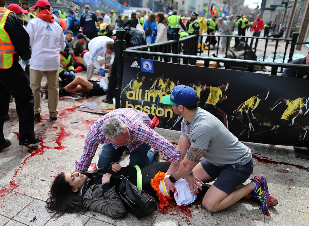 Trecători ajută o femeie rănită la locul primei explozii de pe strada Boylston, aproape de linia de sosire a celui de-al 117-lea Maraton Boston, luni, 15 aprilie 2013.