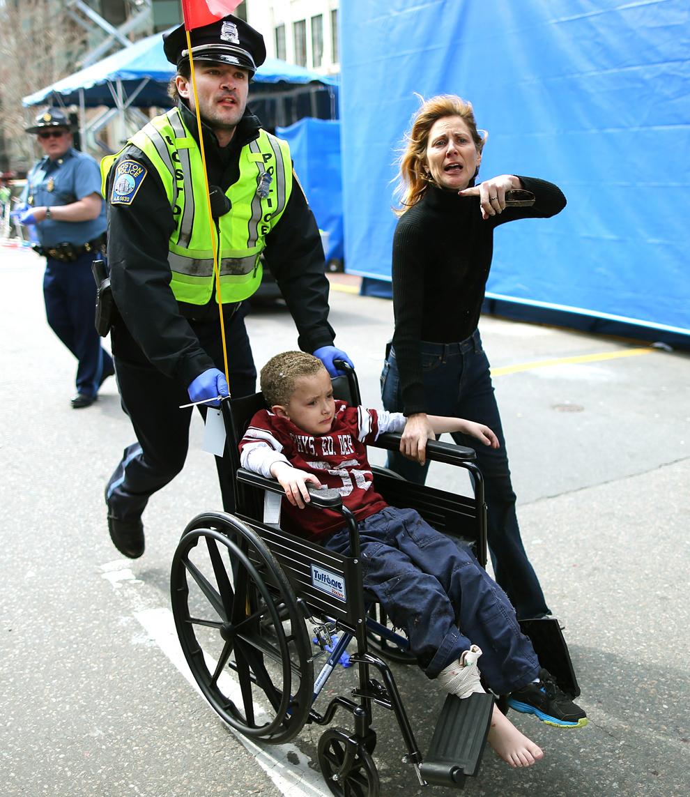 Un poliţist din Boston împinge un carucior cu rotile cu un baieţel rănit în timpul primei explozii de pe strada Boylston, aproape de linia de sosire a celui de-al 117-lea Maraton al oraşului Boston, luni, 15 aprilie 2013.
