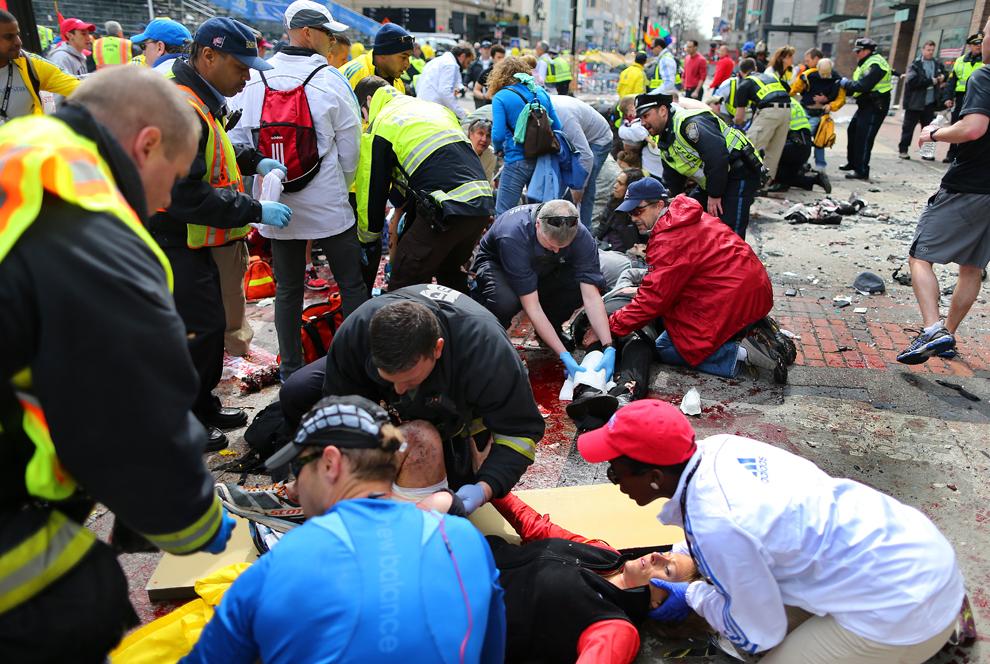 Echipaje medicale acordă primul ajutor unor persoane rănite,  după ce două explozii au avut loc aproape de linia de sosire a celui de-al 117-lea Maraton Boston, luni, 15 aprilie 2013.