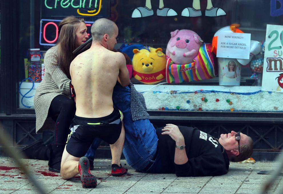 Trecători acordă primul ajutor unei persoane rănite, după ce două explozii au avut loc aproape de linia de sosire a celui de-al 117-lea Maraton Boston, luni, 15 aprilie 2013.