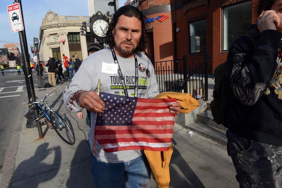 Carlos Arredondo, ţine în mână un steag pătat cu sânge, în timp ce părăseşte locaţia unde au avut loc două explozii, în timpul celui de-al 117-lea Maraton Boston, luni, 15 aprilie 2013.