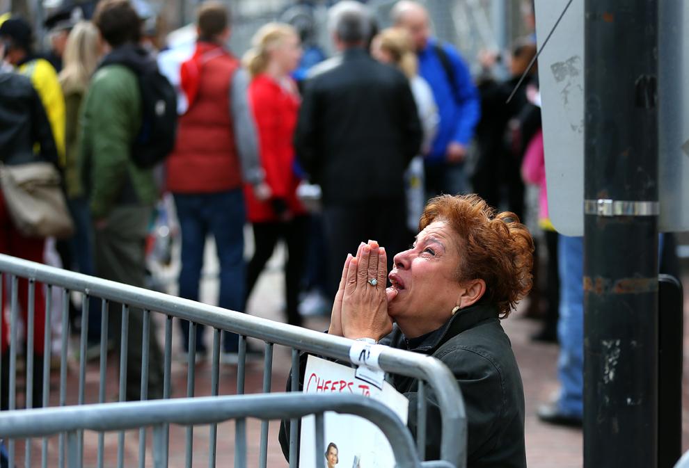 O femeie ce se roagă, ingenunchează la locul primei explozii, pe strada Boylston aproape de linia de sosire a celui de-al 117-lea Maraton al oraşului Boston, luni, 15 aprilie 2013.