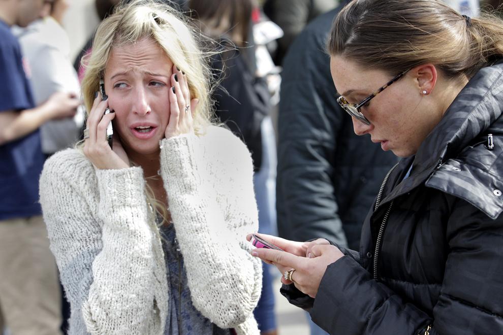 Două femei vorbesc la telefon, după ce două explozii au avut loc aproape de linia de sosire a celui de-al 117-lea Maraton Boston, luni, 15 aprilie 2013.
