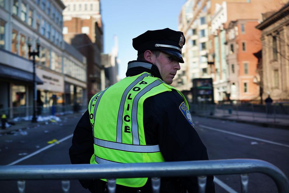 Un poliţist stă lângă zona unde au avut loc cele două explozii,în timpul maratonului oraşului Boston, marţi, 16 aprilie 2013.
