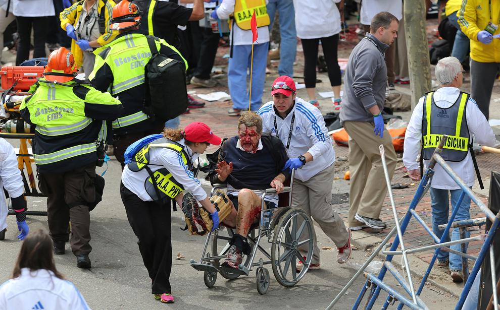 Un bărbat rănit în timpul primei explozii este transportat cu un carucior cu rotile, în Boston, luni, 15 aprilie 2013.